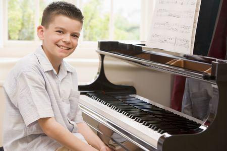 tocando piano: Chico tocando el piano Foto de archivo