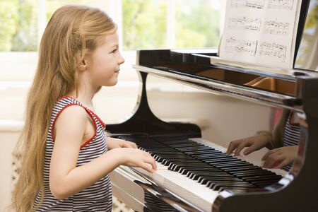 playing instrument: Young Girl Playing Piano Stock Photo
