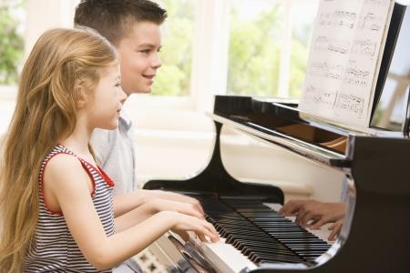 ni�as jugando: Hermano y hermana tocando el piano Foto de archivo