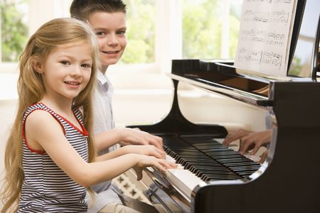 piano: Hermano y hermana tocando el piano Foto de archivo
