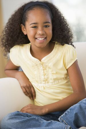 elementary age girls: Young Girl Sitting On A Sofa At Home Stock Photo