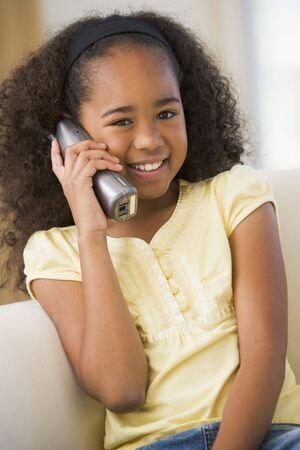 hablando por telefono: Ni�a sentada en un sof�, hablando por un tel�fono