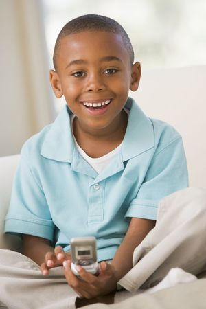 elementary age boy: Young Boy Sitting On A Sofa, Text Messaging