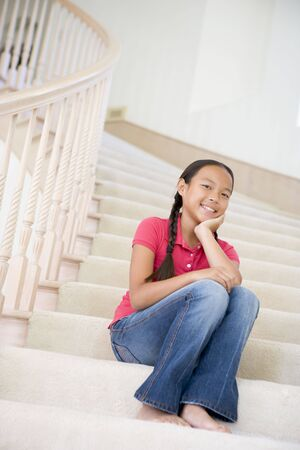 Young Girl Sitting On A Stairwell At Home photo