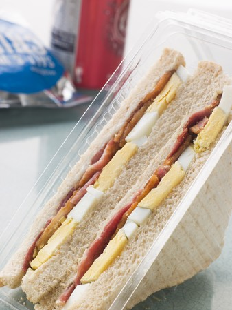 Egg And Bacon Sandwich On White Bread With A Bag Of Crisps And A Can Of Fizzy Drink Stock Photo - 4422472