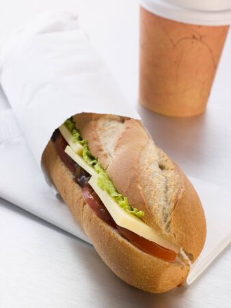 filled roll: Cheddar Cheese, Pickle And Salad Baguette With A Take Away Coffee Stock Photo