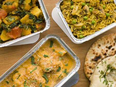 junk food: Selection Indian Take Away Dishes In Foil Containers Stock Photo