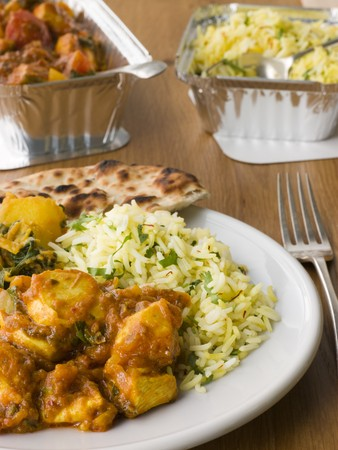 takeaway: Plate Of Indian Take Away- Chicken Bhoona, Sag Aloo, Pilau Rice And Naan Bread Stock Photo