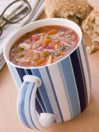 Cup Of Vegetable And Pasta Soup With A Granary Bread Roll photo