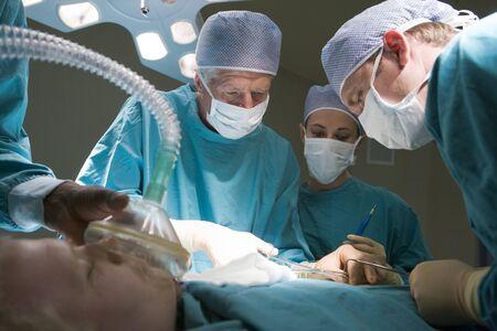 quirurgico: Tres cirujanos que operan en un paciente