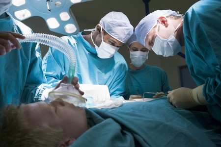 Drie chirurgen die een patiënt