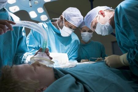 cirujano: Tres cirujanos que operan en un paciente