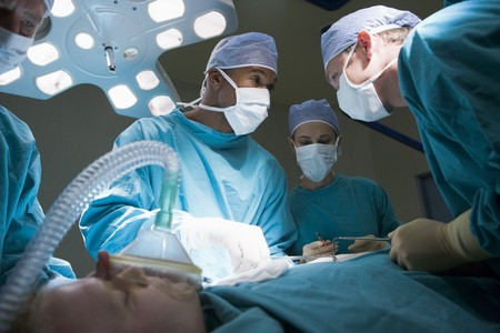 operate: Three Surgeons Operating On A Patient