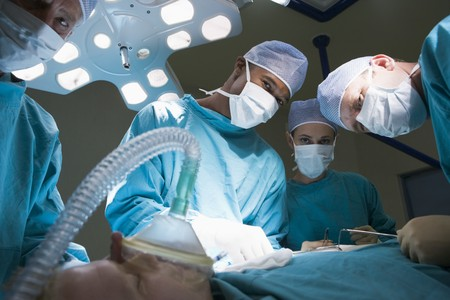 Three Surgeons Operating On A Patient photo