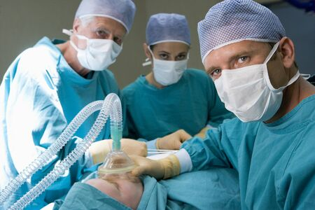Three Surgeons Operating On A Patient Stock Photo - 4446547
