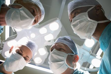 medical lighting: Low Angle View Of Four Surgeons