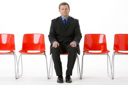 Businessman Sitting In Row Of Empty Chairs  photo