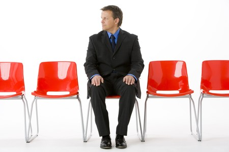 Businessman Sitting In Row Of Empty Chairs  Stock Photo - 4444502