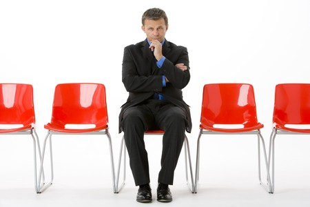 sit studio: Businessman Sitting In Row Of Empty Chairs