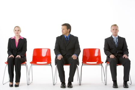 Three Business People Sitting On Red Plastic Seats  photo