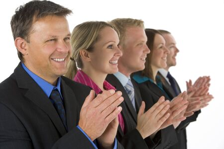 Group Of Business People In A Line Smiling And Applauding photo