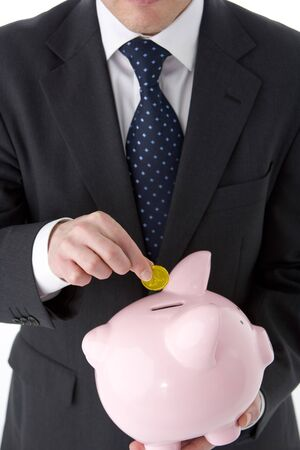 Businessman Putting Coin Into Piggy Bank  Stock Photo - 4444736