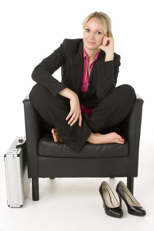 Businesswoman Sitting In Leather Chair With Her Shoes Off photo