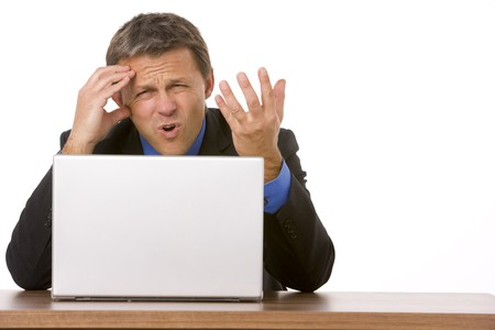Businessman Frowning While Looking At Laptop Stock Photo - 4444461