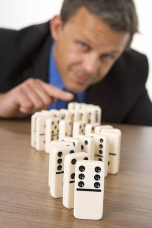 Businessman Playing With Dominos Stock Photo - 4444577
