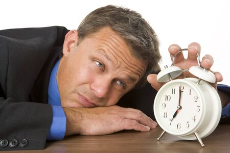 tired businessman: Businessman Leaning On Desk Watching Clock Stock Photo