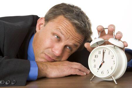 epuise: Homme d'affaires en s'appuyant sur Desk Clock Watching