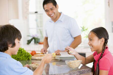 preteen asian: Children Having Breakfast While Dad Prepares Food