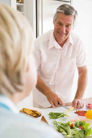 mealtime: Husband Talking To Wife While Preparing meal,mealtime Stock Photo