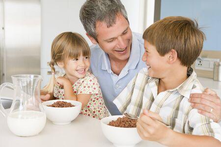ni�os desayuno: Sentado padre con ni�os que comen desayuno