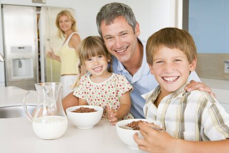Father With Children As They Eat Breakfast And Mother In The Back Ground  Stock Photo - 4445301