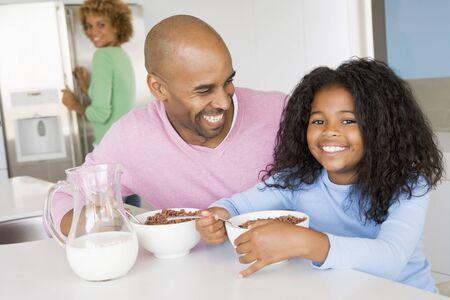 comiendo cereal: Padre Sentado Con Hija Como Ella que comen desayuno con su madre en el fondo