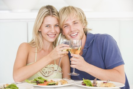 pareja en casa: Pareja joven Disfrutar de la comida, la hora de la comida con una copa de vino