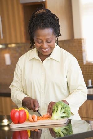 one senior adult woman: Mujer cortar vegetales