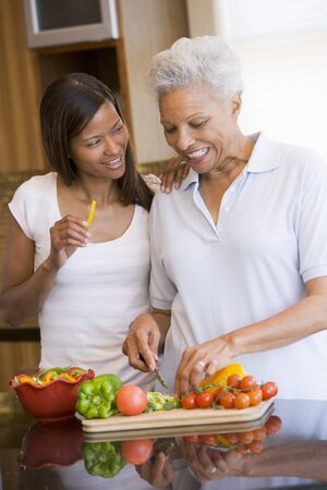 mealtime: Mother And Daughter Preparing A meal,mealtime Together Stock Photo