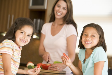 hispanic kids: Girls Eating Pepper Strips While Mother Is Preparing meal,mealtime Stock Photo