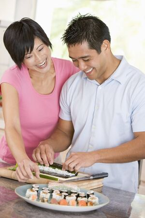 Couple Preparing Sushi Together Stock Photo - 4446254