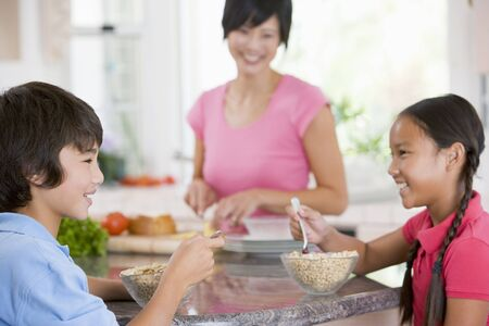Children Enjoying Breakfast While Mother Is Preparing Food photo
