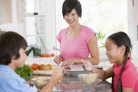 preteen asian: Children Enjoying Breakfast While Mother Is Preparing Food Stock Photo
