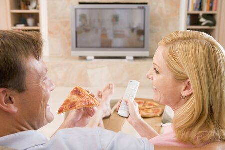 Couple Enjoying Pizza In Front Of TV photo