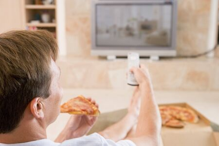over eating: Man Enjoying Pizza While Watching TV Stock Photo