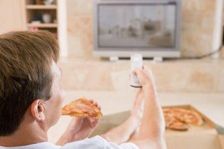 personas viendo television: Pizza Si bien el hombre goza de ver televisi�n Foto de archivo