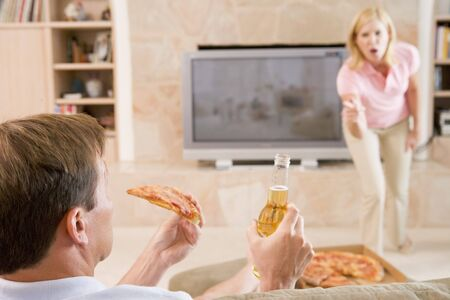 Wife Telling Husband Off For Drinking Beer And Eating Pizza photo