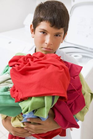 domestic chore: Young ni�o con una pila de ropa sucia