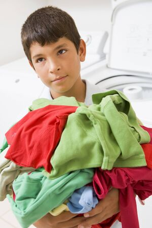 Young Boy Holding A Pile Of Laundry photo