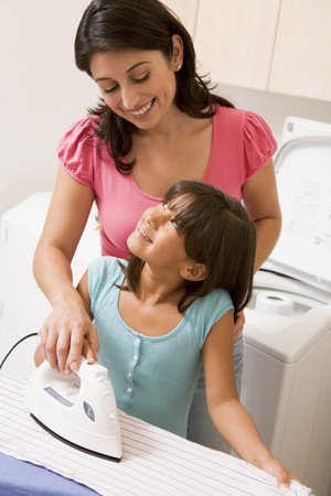 helping children: Mother And Daughter Ironing